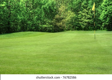 Beautiful vivid colorful image of golf course with green and fairway on sunny day