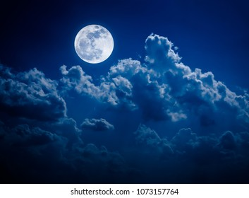 Beautiful vivid skyscape. Landscape of night sky with bright full moon and cloudy, serenity blue nature background. Outdoor at nighttime with moonlight. The moon taken with my own camera.