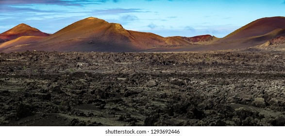 Beautiful volcanic landscape background. Mountain range with lava fields in the foreground. Lanzarote, Canary Islands.