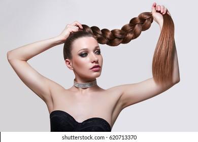 Beautiful voluminous long silky braid. Girl with long hair. Straightening of keratin. Hair care. Beauty saloon. Hair care, spa. Retro. Bright makeup. Healthy hair, long, thick braid.