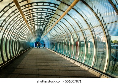 Beautiful Vortex like Pedestrian bridge showing vision and concept of architecture with two women friends walking down during evening sunset in canary wharf of London