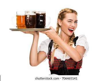 beautiful waitress in traditional german costume winking and holding beer glasses on Oktoberfest, isolated on white