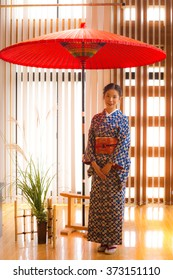 Beautiful waitress wearing kimono standing under traditional Japanese red umbrella was greeting to guests.