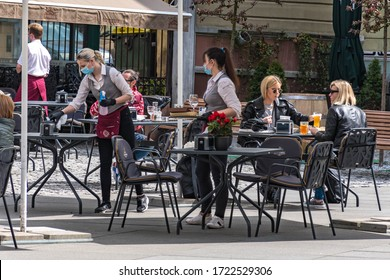 Beautiful waitresses wearing masks, preparing and disinfecting the tables and chairs, outdoor bar, reopening café or restaurant with blonde girls drinking and eating at the table, restrictions ease