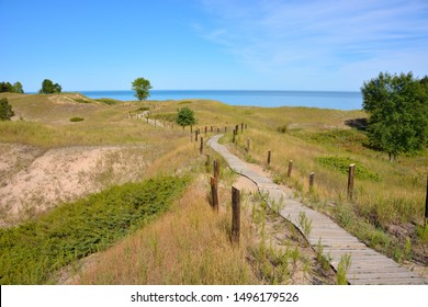Beautiful walkway through the natural sand dunes along the Great Lake shores. The Kohler Andrea park is in the area around Sheboygan and Wilson Wisconsin. Small trees and Juniper bushes along path.