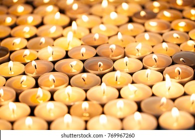 Beautiful warm orange glow of candlelight from many lit tea light candles. Many candles burning bright. Selective focus on central candle flames.