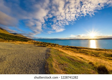 Beautiful warm sunset on the turquoise water of Lake Pukaki formed by rivers Hooker and Tasman. Aoraki / Mount Cook National Park, South Island, New Zealand.