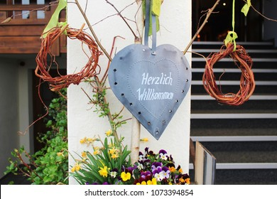 """Beautiful warm welcome with metall heart with the german words """"Herzlich Willkommen"""" -  English: Cordial welcome, decorated with spring flowers"""