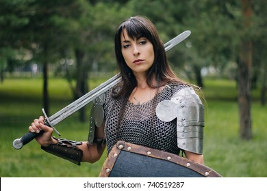 A beautiful warrior girl in a chain mail, a sword and a shield in her hand. A woman with long black hair in the image of an Amazon, a Viking. Fantasy. Medieval armor