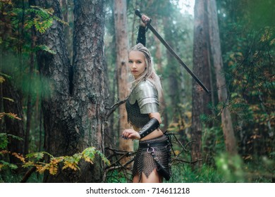 A beautiful warrior girl with a sword and in armor. A model in a chain skirt and a vest in a mysterious forest. Fantasy photo.