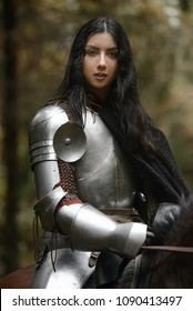 A beautiful warrior girl with a sword wearing chainmail and armor riding a horse in a mysterious forest