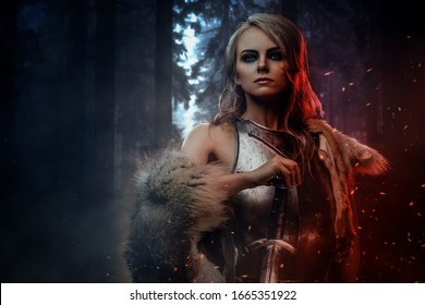Beautiful warrior woman holding a sword wearing steel cuirass and fur in night forest. Fantasy fashion.