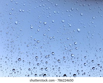Beautiful water drops on glass against nice blue sky