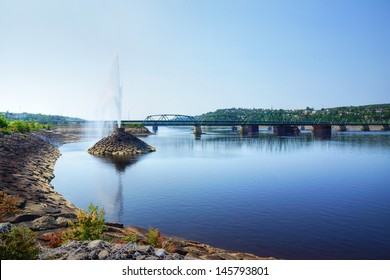 Beautiful water fountain in a river by a bridge, public park in Saguenay, Quebec, Canada