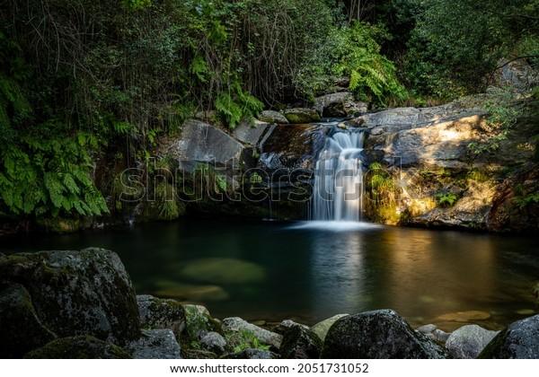 Beautiful water stream in Poço da Cilha waterfall, Manhouce, São Pedro do Sul, Portugal. Long exposure smooth effect. Idyllic green scenery, mountain forest landscape.