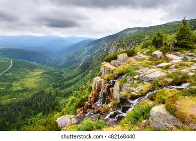 Beautiful waterfall above a deep green valley in summer mountains
