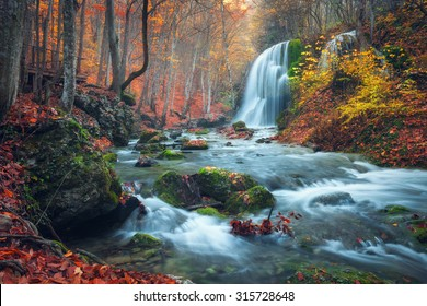 Beautiful waterfall in autumn forest in crimean mountains at sunset. Silver Stream Waterfall in Grand Canyon Of Crimea.