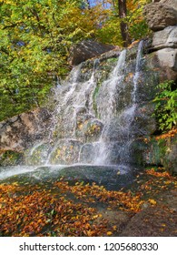 Beautiful waterfall with blurred flowing streams of water against the background of fallen autumn leaves and the green covering of mold stones, nature, Sofiyivka, Ukraine