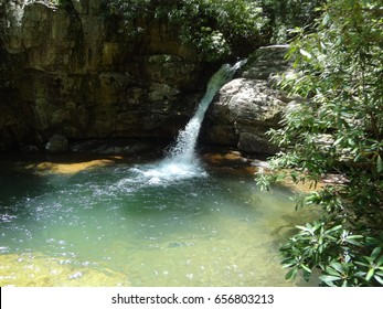 A beautiful waterfall cascading into a large pool at the Blue Hole in East Tennessee, USA.