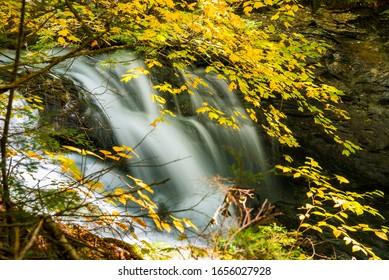 Beautiful waterfall with a colourful tree branches in foreground on a sunny autumn morning