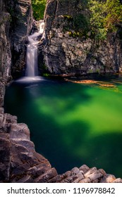 Beautiful waterfall falling through rocks and forming a deep lake on the Fonias river on Samothrace Island in Greece with leaves foliage moving on the surface