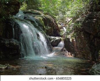 A beautiful waterfall hidden in the woods on a bright and sunny day. The Blue Hole, East Tennessee. USA.