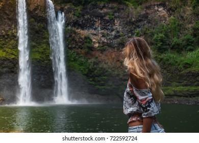 beautiful waterfall in Kauai Hawaii, back of sexy woman. Woman looks at waterfall. Young pretty woman enjoying waterfall view  . Wailua Falls