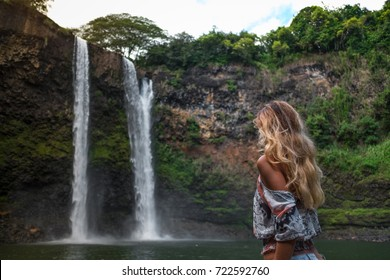 beautiful waterfall in Kauai Hawaii, back of sexy woman. Woman looks at waterfall. Young pretty woman enjoying waterfall view  . Wailua Falls