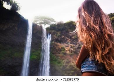 beautiful waterfall in Kauai Hawaii, back of sexy woman with long hair. Woman looks at waterfall  . Wailua Falls