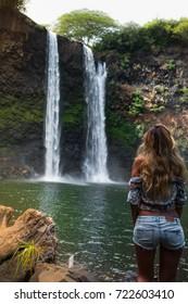 beautiful waterfall in Kauai Hawaii, back of sexy woman. Woman looks at waterfall Wailua Falls