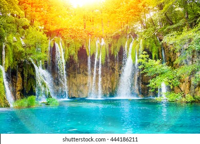 Beautiful waterfall landscape. Green forest with sun light, pond and water stream.