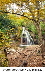 Beautiful waterfall at mountain river in colorful autumn forest. Nature landscape