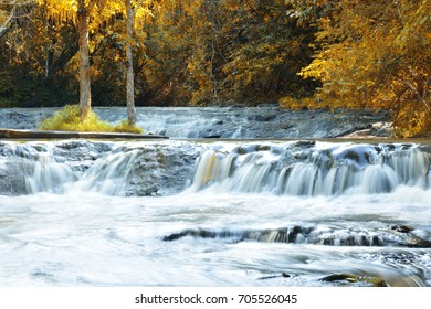Beautiful waterfall at mountain river in colorful autumn forest with  orange leaves at sunset. Nature landscape. Orange leave looked as autumn tone.