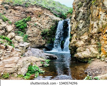 Beautiful Waterfall in Nature with Water Streaming through Mountain Cliffs into Pool
