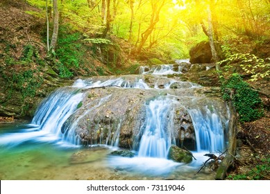 beautiful waterfall in a rays of sparkle sun
