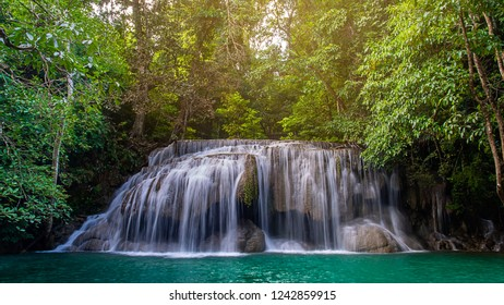A Beautiful waterfall  scene has several streams of water with sunlights and surrounded by lush trees in deep forest of Erawan National Park in Kanchanaburi Province , Thailand.