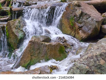 Beautiful waterfall streams on the mountain river flowing among stones, rocks and forest in the Altai mountains, Russia.