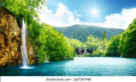 Beautiful waterfall with a stunning forest in the background on a nice sunny day.