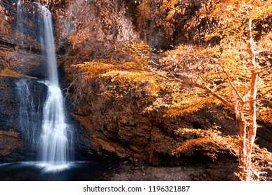 beautiful waterfall in woods in autumn season with sunny lights on the trees