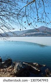 Beautiful waterfront scene at half frozen lake Orestiada  in Kastoria Greece a sunny winter day