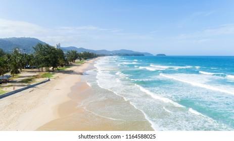 Beautiful wave crashing on sandy shore at karon beach in phuket thailand,aerial view drone shot