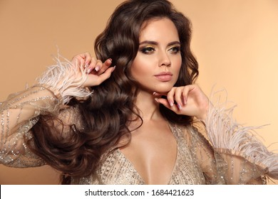 Beautiful wavy hairstyle. Beauty portrait of sexy brunette woman. Gorgeous girl model with makeup, long healthy hair style posing isolated on studio beige background.