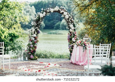 Beautiful wedding altar made of roses stands in the garden