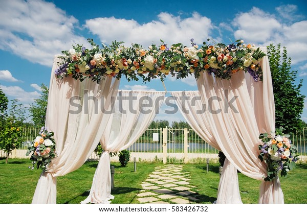 Beautiful wedding arch, decorated with biege cloth and flowers
