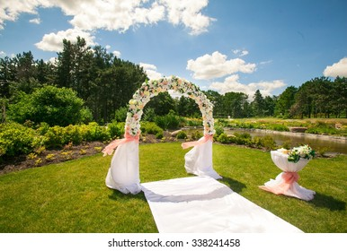 A beautiful wedding arch for newlyweds, decorated with flowers, against the blue sky in the summer garden