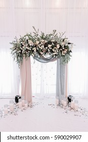 Beautiful wedding archway. Arch decorated with peachy and silvery cloth and flowers
