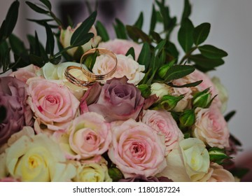 Beautiful wedding bouquet of the bride from roses and wedding rings