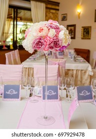 Beautiful wedding bouquet of creamy and pink roses in glass vase on dinner table. Table setting at luxury wedding reception. Flowers on the table