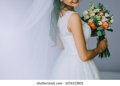 Beautiful wedding bouquet in hands of the bride in white wedding dress