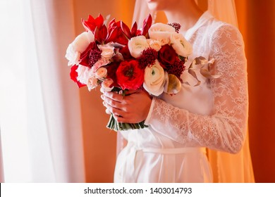 Beautiful wedding bouquet in hands of the bride. Trendy and modern wedding flowers. Woman in bathrobe in hotel room. Flower composition red, rose, burgundy and marsala color.